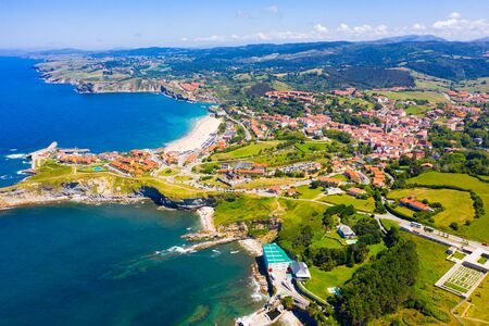Picturesque aerial view of green valleys on Cantabrian Sea coastal area with brownish roofs of houses of Comillas village, Spain