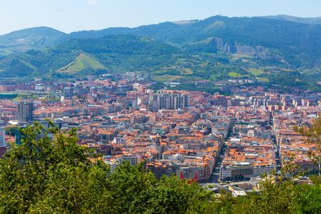 General view of Spanish city of Bilbao on background of picturesque mountain landscape in sunny summer day Stock Photo