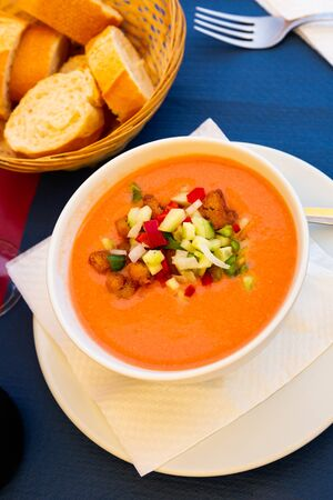Traditional Spanish refreshing pureed soup gazpacho from tomatoes served with fried bread and chopped vegetables