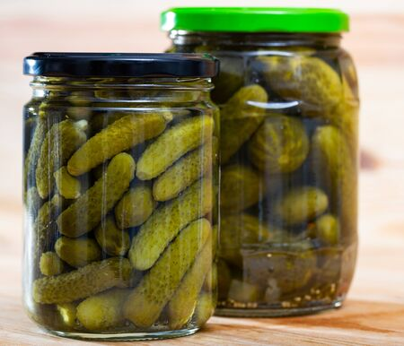 Glass jar with pickled cucumbers on a wooden table