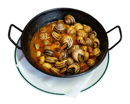 Appetizer of escargots stewed with chorizo served in black fry pan. Spanish cuisine. Isolated over white background