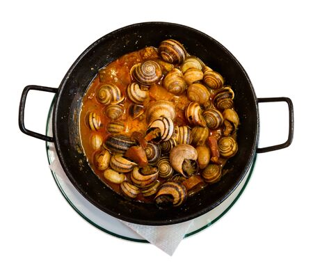 Top view of black frypan with traditional Spanish tapa Caracoles en salsa - snails stewed to homemade in gravy. Isolated over white background