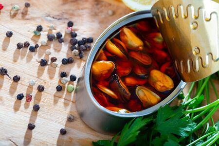 Closeup view of opened can of Spanish style marinated mussels in oil on wooden table with lemon and greens