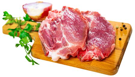 Sliced raw pork chop with parsley and onion. Isolated over white background 写真素材