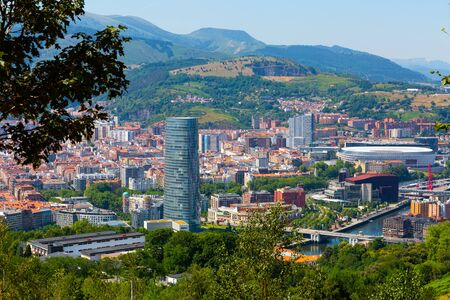 Scenic panoramic view of modern Bilbao cityscape surrounded by mountain ranges in summer, Spain