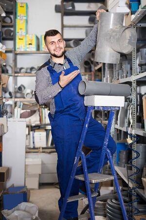 Smiling workman inspecting drain pipe detail in workshop