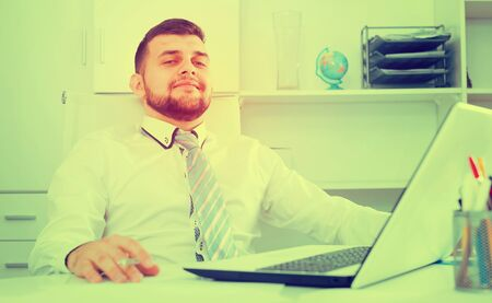 Male employee having productive day at work in office