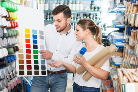 Young family couple standing with tools using palette scheme in paint store