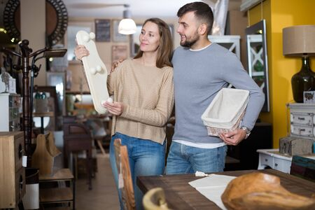 Handsome guy with girlfriend buying original wall hanger in furniture store Stockfoto
