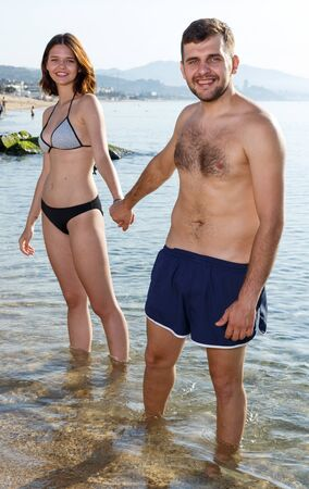 Young couple dressed in beachwear walking on the beach