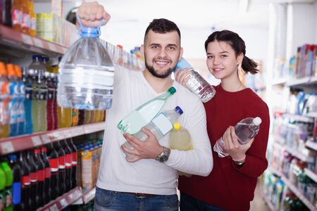 Portrait of smiling customers standing at beverages section of supermarket
