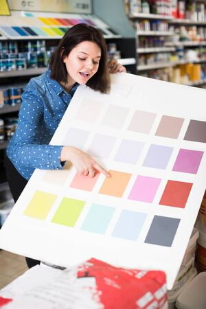 friendly female customer examining color scheme variants in paint supplies store