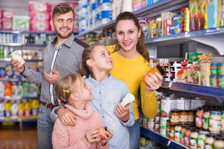 Happy parents with two daughters choosing a fresh products in the food store