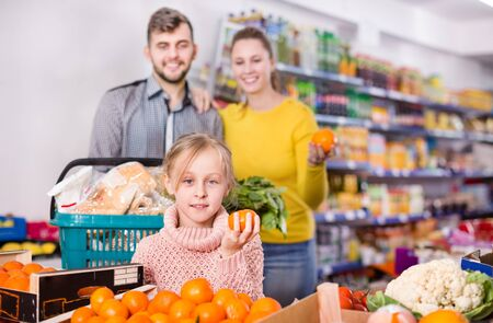 Happy little girl with loving parents choosing sweet mandarins in supermarket