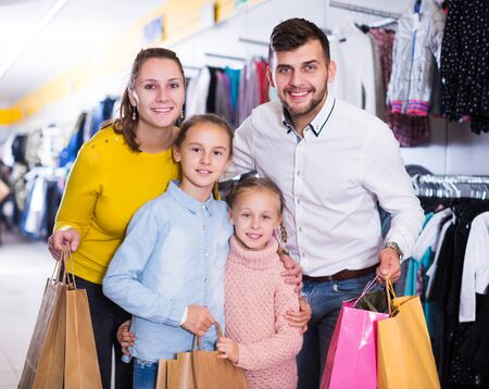 Portrait of happy parents with two little girls during family shopping