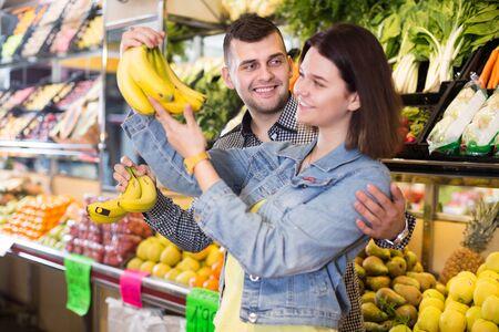 Jeune couple d'amoureux décidant de fruits dans une épicerie Banque d'images
