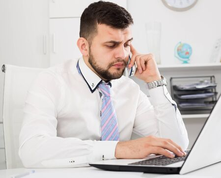 Young male worker working productively on project in office
