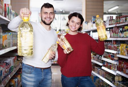 Young family selecting vegetable oil at grocery store Banco de Imagens