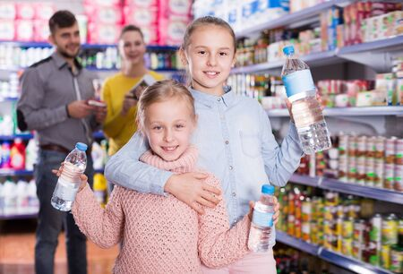 Two small nice sisters holding bottled water during family shopping in supermarket