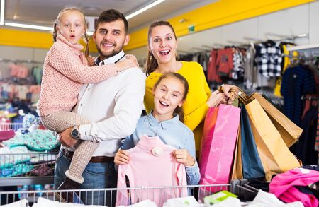 Young cheerful family with two daughters after shopping in clothes shop