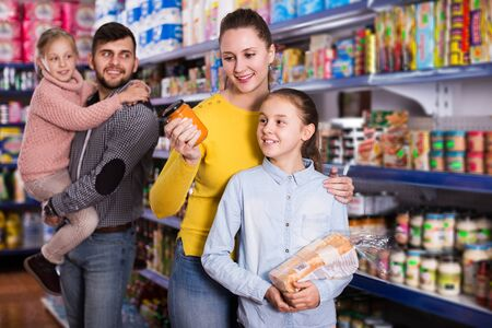 Young family of four shopping together in grocery store