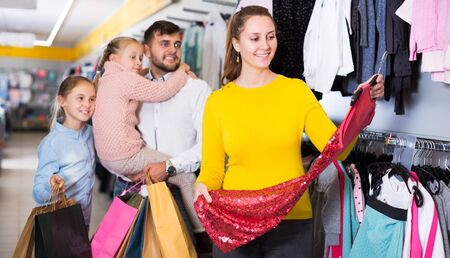 Smiling woman with husband and daughters choosing evening dress in clothing store Stock Photo