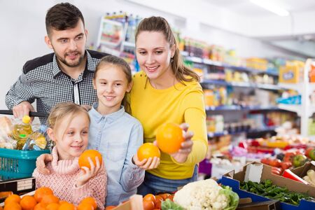Young family of four shopping together in greengrocery store choosing the oranges 版權商用圖片