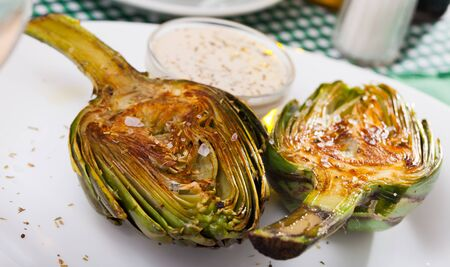 Appetizing roasted halves of artichokes served with coarse salt and sauce Reklamní fotografie