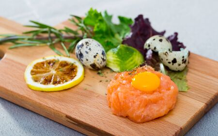 Fresh salmon tartar with quail egg and spices on wooden board