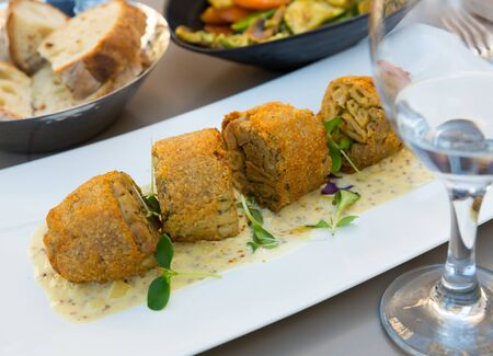 Fried breaded pieces of traditional French Andouillette served with spicy sauce and microgreens