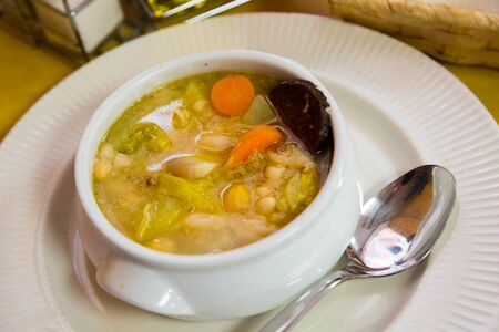 Thick Catalan soup escudella with mix of vegetables, meat and traditional black sausage butifarra