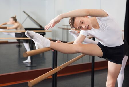 Teenager and women practicing at the ballet barre Banco de Imagens