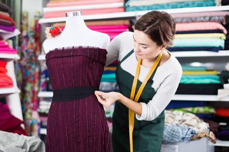 Female tailor finishing work at festive dress at studio Imagens