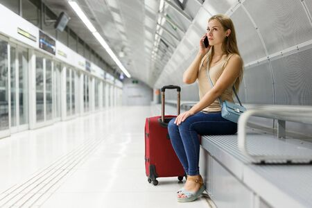 Young girl traveler with red suitcase sitting and waiting at underground platform Imagens