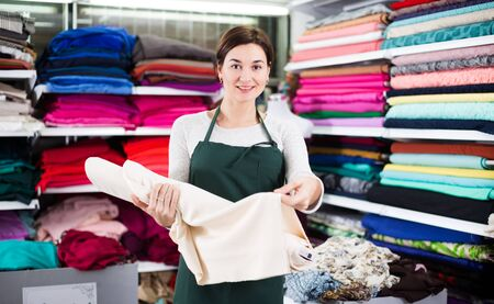 Young woman seller displaying white fabric at drapery shop