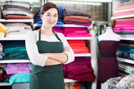 Young woman seller displaying various fabrics at drapery shop