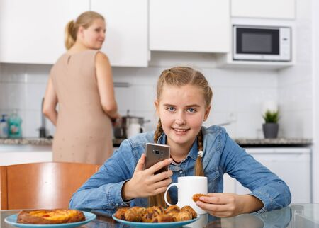 Teenage girl drinking tea and eating croissants while her mother taking care of her