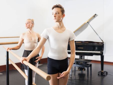 Choreographer woman and young man do exercises at ballet bar in hall with mirror