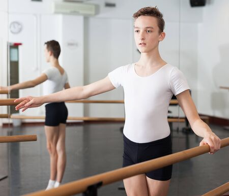 Positive teenager practicing at the ballet barre