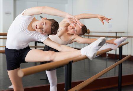 Graziosa donna e giovane posano in sala con balletto bar