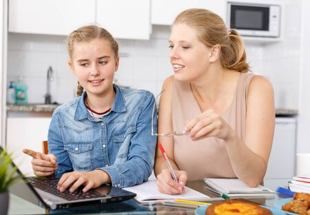 Attractive woman helping her teenage daughter to do her homework in kitchen
