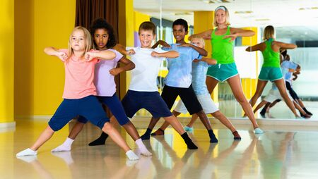 Cheerful  smiling preteen dancers practicing dance routine with female choreographer in modern studio