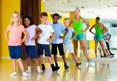 Happy cheerful positive  preteen boys and girls practicing dance, stretching with female trainer in dance hall Banco de Imagens