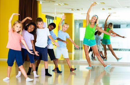 Group of tweens training movements of modern dance in choreography studio with female trainer Banco de Imagens