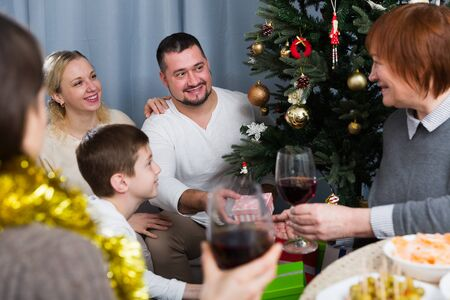 Happy family celebrating Christmas together, cheerful man presenting gifts Stockfoto