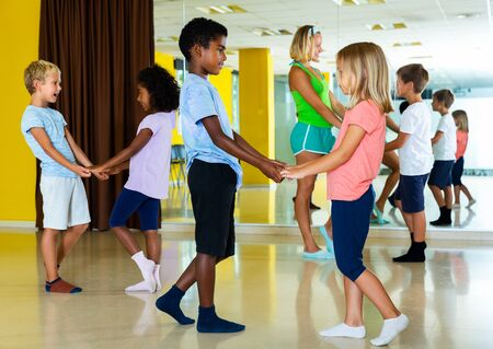 Group of preteen kids training movements of slow foxtrot in dance studio with female coach