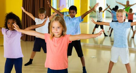 Portrait of smiling children practicing sport dance in modern dance hall 写真素材