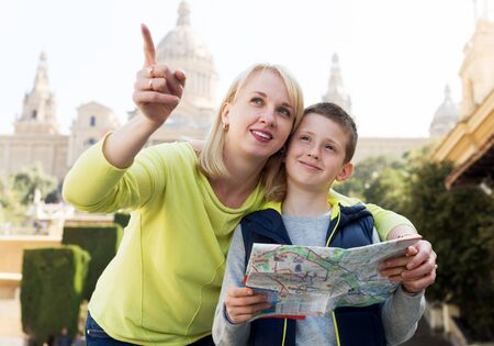 Glad mother and son consulting map guide during sightseeing tour