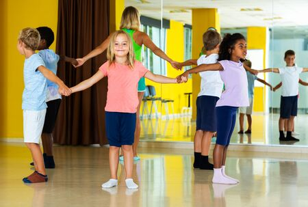 Group of children with their teacher holding hands and dancing in circle in dance class