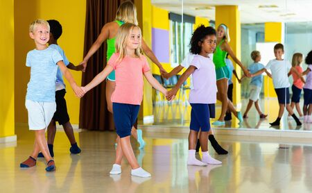 Group of glad positive  tweens exercising folk dance, forming circle with female coach in choreography class